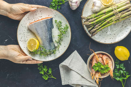 Woman holds ceramic plate with raw trout fish, thyme and lemon in hands on black concrete table surface surrounded plates with fresh raw asparagus, shrimp, prawn, parsley. Healthy seafood background. Stock Photo