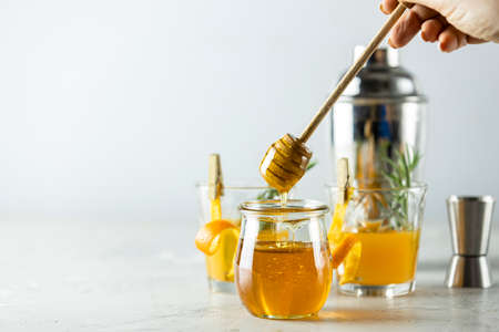 Woman hand holds a spoon for honey over jar in front of two glasses of honey bourbon cocktail with rosemary syrup or homemade whiskey sour with orange peel and rosemary decoration and bartender tools