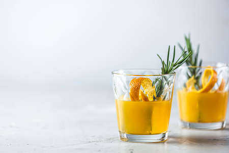 Two glasses of honey bourbon cocktail with rosemary simple syrup or homemade whiskey sour cocktail drink with orange and rosemary decoration orange peel, jar of honey and bartender tools