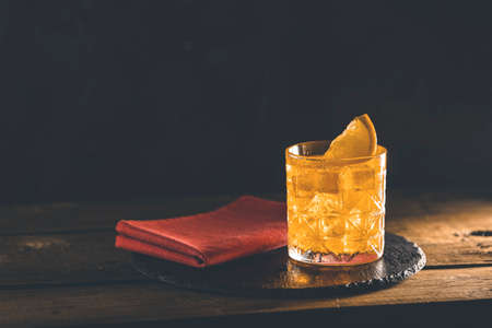 Glass of the cocktail negroni with red napkin and black stone tray on a old wooden board. Decorated orange slice. Nice romantic backlight. Stock Photo