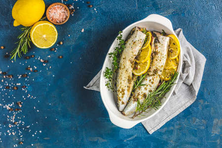 Mackerels served on white dish with lemon, thyme, rosemary and spices. Raw marinated fishes on classic blue surface. Seafood background.