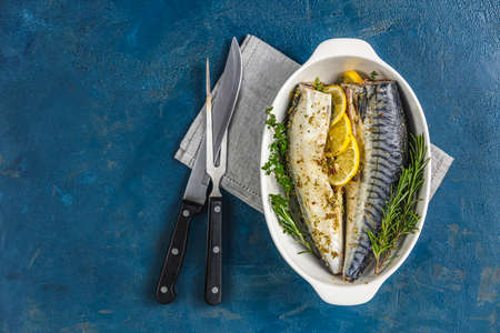 Mackerels served on white dish with lemon, thyme, rosemary and spices. Raw marinated fishes with cutlery on classic blue surface. Seafood background.