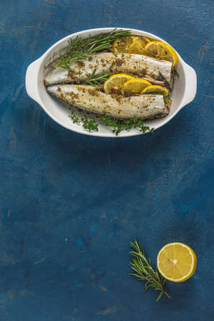Mackerels served on white dish with lemon, thyme, rosemary and spices. Raw marinated fishes on classic blue surface. Seafood flat lay background with copy space for you text.