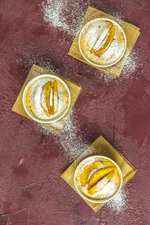 Three apple pies in ceramic baking molds ramekin with parchment  on dark red concrete table. Top view, flat lay. Stock Photo