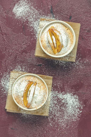 Two apple pies in ceramic baking molds ramekin with parchment  on dark red concrete table. Top view, flat lay.