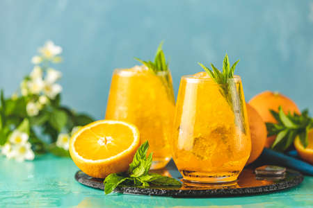 Two glass of orange ice drink with fresh mint on wooden turquoise table surface. Fresh cocktail drinks with ice fruit and herb decoration. Alcoholic non-alcoholic beverage. Mojito on blue background