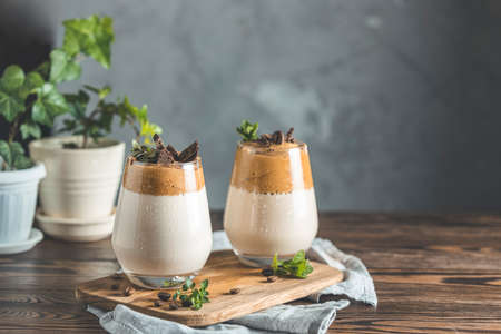 Two glasses with Dalgona frothy coffee trend korean drink latte espresso with coffee foam, decorated by thyme and dark chocolate. Dark wooden table surface Stock Photo