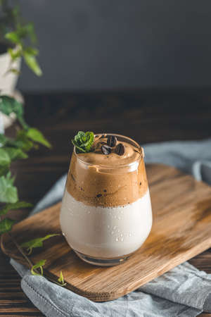 Glass with water drops of Iced Dalgona Coffee, a trendy fluffy creamy whipped coffee, decorated by fresh mint and coffee beans. Dark rustic style. Stock Photo