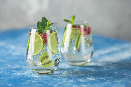 Detox water or martini tonic cocktail with kiwi, lime and ice, decoration pomegranate and mint. Summer fresh lime soda cocktail, selective focus Stock Photo