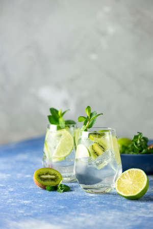 Two detox water or martini tonic cocktail with kiwi, lime, ice and mint. A new kind of mojito with kiwi, lime and mint and of course ice Stock Photo