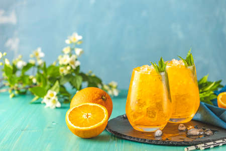 Two glass of orange ice drink with fresh mint on wooden turquoise table surface. Fresh cocktail drinks with ice fruit and herb decoration. Alcoholic non-alcoholic drink-beverage. Stock Photo