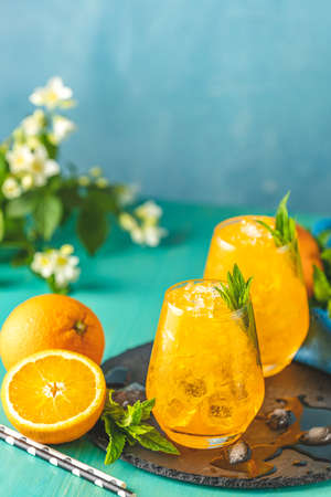 Orange drink with ice. Two glass of orange ice drink with fresh mint on wooden turquoise table surface. Alcoholic non-alcoholic drink-beverage