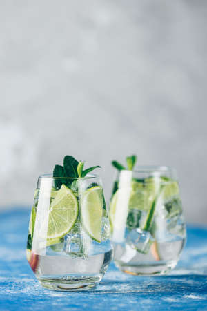 Two detox water, mojito or martini tonic cocktail with kiwi, lime, ice, mint. Summer fresh lime soda cocktail, selective focus. A new kind of mojito with kiwi, lime and mint and of course ice Stock Photo