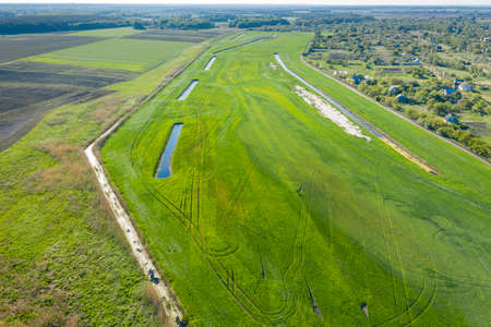 Land improvement or land amelioration concept, drone flying over narrow irrigation or drainage channels on rye or wheat field. Illustration of agriculture in the zone of risky agriculture.