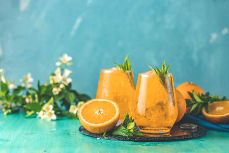 Two glasses of orange ice drink with fresh mint on wooden turquoise table surface. Fresh cocktail drinks with ice fruit and herb decoration. Alcoholic non alcoholic beverage, summer fresh drink