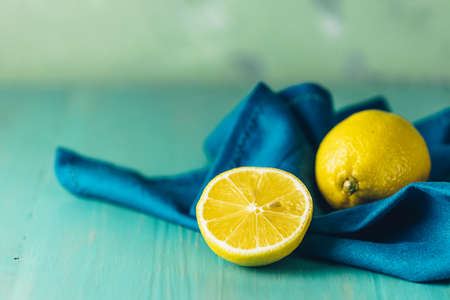 Ripe juicy lemon on wooden turquoise table surface. Close up, copy space for you text, shallow depth of the field. Stock Photo