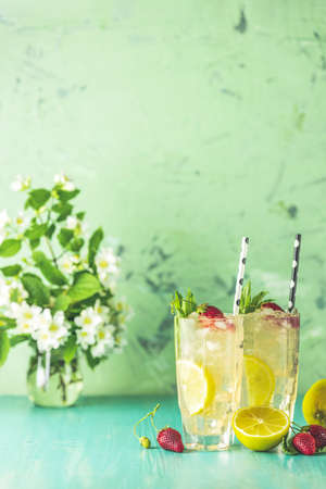 Two glasses of cold icy refreshing drink with lemon and strawberry served with bar tools on green wooden table with white blooming flowers. Fresh cocktail drinks with ice fruit and herb decoration. Stock Photo