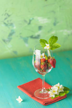 Fresh ripe raw strawberry with green leaves in the wine glass on green surface with red napkin.