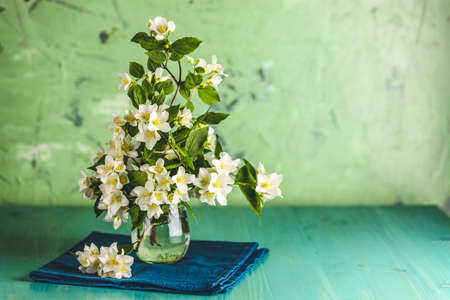 Beautiful jasmine bouquet on light green wooden surface table. Holiday greeting card with copy spice for you text. Stock Photo