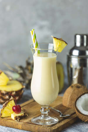 Glass of tasty Frozen Pina Colada Traditional Caribbean cocktail decorated by slice of pineapple, served on light wooden cutting board