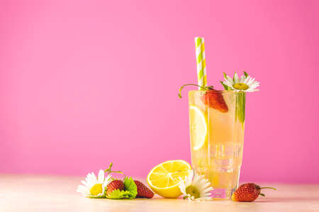 Glasses of cold icy refreshing drink with lemon and strawberry. Bright pink background.  Fresh cocktail drinks with ice fruit, herb and chamomile decoration. Stock Photo