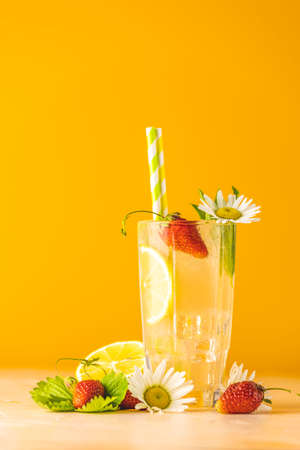 Glasses of cold icy refreshing drink with lemon and strawberry. Bright yellow background.  Fresh cocktail drinks with ice fruit, herb and chamomile decoration. Stock Photo