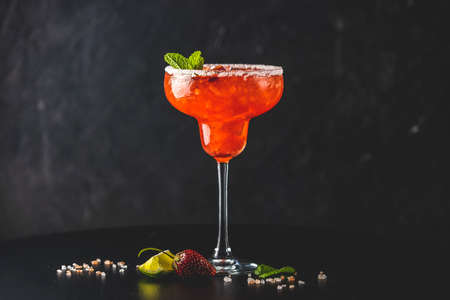 Frozen strawberry lime mint margarita in tall footed glass on the dark background. Luxury alcohol fresh drink