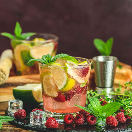 Refreshing mint cocktail mojito with rum, lime, mint, thyme, ice and raspberry. Alcohol or non alcohol summer fresh drink. Stock Photo