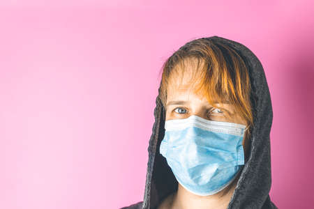 Tired female medical volunteer in a medical mask and hood on a pink background. Health protection during flu virus outbreak, coronavirus epidemic infectious diseases and air pollution in the city