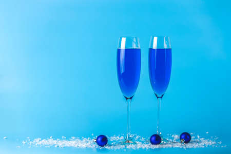 Two wineglasses of blue champagne  on a blue background with Christmas an New Year decor. Shallow depth of the field, copy space for you text.