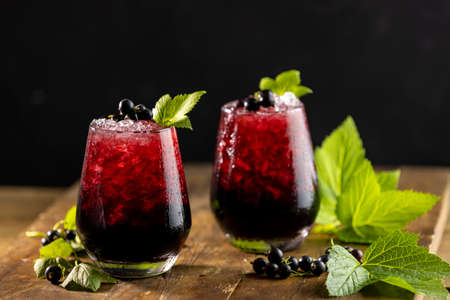 Two glass of cold ice black currant juice or cocktail with ripe berries and green leaves on dark wooden table. Alcohol or non alcohol summer fresh drink Stock Photo