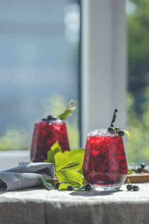 Two glass of cold ice black currant juice with ripe berries and green leaves on table in sunny room near window with garden outside