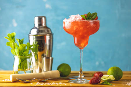 Frozen strawberry lime mint margarita in tall footed glass close up on the wooden table with bar tools and ingredients. Luxury alcohol fresh drink.