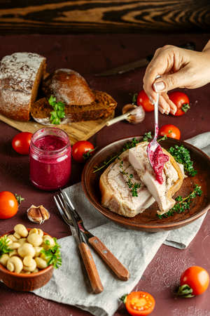 Woman dressing tasty baking pork lard bacon fatback with black pepper and other herbs and spices in ceramic dish. Traditional Ukrainian, Hungarian, Polish or other Eastern Europe national dish Imagens
