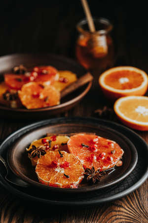 Orange dessert with wine honey or maple syrup and ginger spice, decorated pomegranate berries. Wonderfully sweet, rich and fresh food. Dark rustic background, copy space for you text
