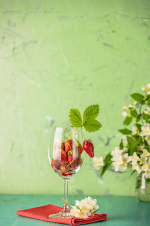 Fresh ripe raw strawberry with green leaves in the wine glass on green surface.