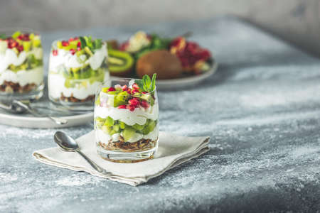 Glass jar of kiwi parfait dessert in glass with ingredients and spoon on gray napkin. Yogurt, granola and fruits. Healthy snack or breakfast. Light gray concrete surface