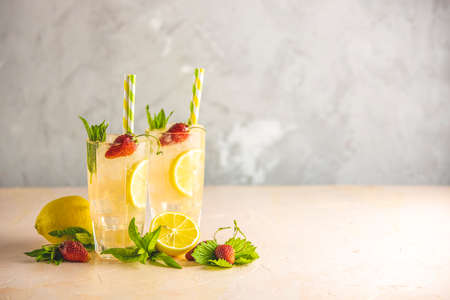 Two glasses of cold icy refreshing drink with lemon and strawberry served with bar tools on light pink table with white blooming flowers. Fresh cocktail drinks with ice fruit and herb decoration.