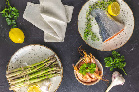 Trout fish surrounded parsley, lemon, shrimp, prawn, asparagus in ceramic plates. Black concrete table surface. Healthy seafood background. 写真素材