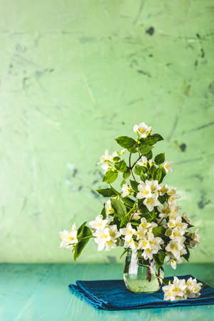 Beautiful jasmine bouquet on light green wooden surface table. Holiday greeting card with copy spice for you text