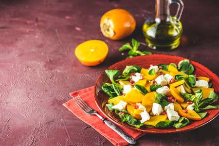 Healthy salad with persimmon, doucette (lambs-lettuce, cornsalad, feld salad) and feta cheese on a red plate on a red background. Superfoods Vitamin autumn or winter persimmon salad 写真素材