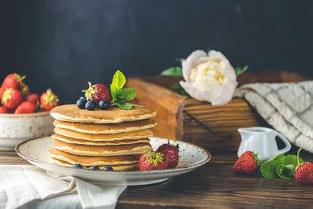 Pancake with strawberry, blueberry and mint in ceramic dish, syrup from small ceramic jar and flowers on a dark wooden table