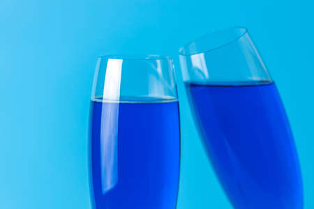 Two wineglasses close up of blue champagne on a blue background. Shallow depth of the field, copy space for you text. 写真素材