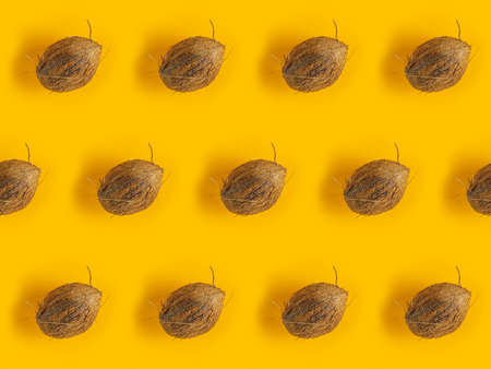 Pattern with ripe coconuts on yellow background. Top View. Copy Space. Pop art design, creative summer concept. Coconut in minimal flat lay style