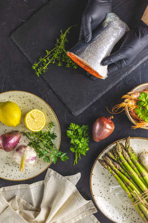 Hands in black gloves support trout fish on black stone cutting board surrounded herbs, onion, garlic, asparagus, shrimp, prawn in ceramic plate Black concrete table surface Healthy seafood background