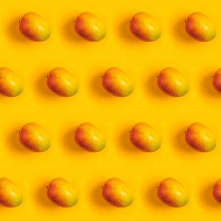 Tropical abstract background. Juicy ripe mango pattern on yellow background top. Seamless pattern with mango. 写真素材