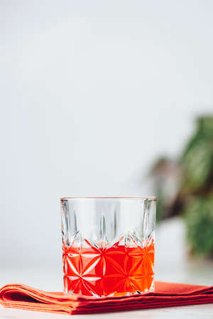 Glass of chocolate red orange negroni, an italian cocktail, an aperitif, first mixed in Firenze, Italy, in 1919, alcoholic bitter cocktail served on the light gray table