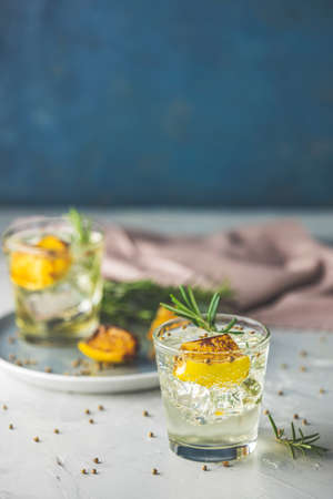 Two glasses of Charred Lemon, Rosemary and Coriander Gin and Tonic is a flavors are perfectly balanced refreshing cocktail. on dark background, close up. 写真素材