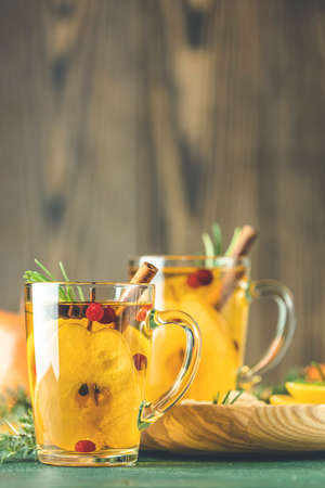 Two glass cup of festive winter drinks, pear cider spice cocktail. Hot drink cocktail for Christmas, winter or autumn holidays. Copy space for you text