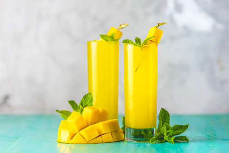 Refreshing summer cocktails made of mango, cold drink or a drink with ice on a blue gray background. Fresh summer ice cold mango cocktail or juice with mint and mango fruit 写真素材